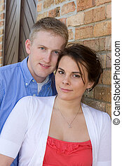 Young Adult Couple - A young adult couple lean against a...