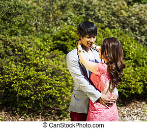 Young Adult Couple Embracing Outdoors