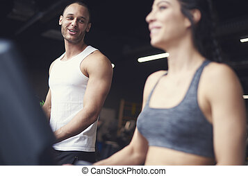 Young adult couple exercising on treadmill