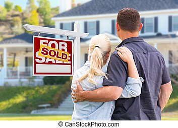 Young Adult Couple Facing Front of Sold Real Estate Sign and House