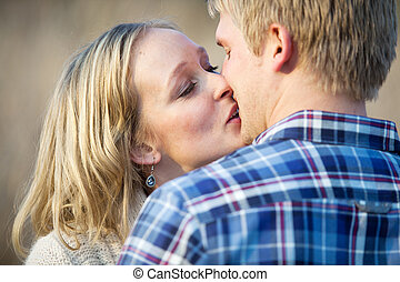 Young adult couple kissing outside in daytime