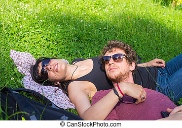 Young adult couple lying down on lush green grass in park,...