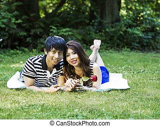 Young Adult Couple Lying on Blanket Outdoors