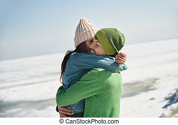 Young adult couple outdoors having fun in winter landscape