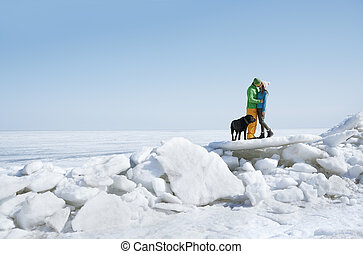 Young adult couple outdoors kissing in winter landscape