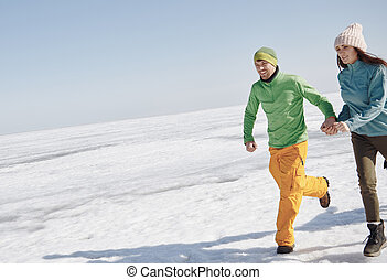 Young adult couple outdoors running in winter landscape