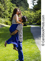 Young Adult Couple Playing Around while Walking Outdoors
