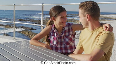 Young adult couple relaxing at the seaside - Side view of a ...