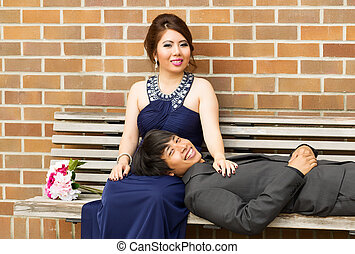 Young Adult Couple Resting on Wooden Bench