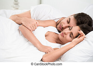 Young adult couple sleeping in bedroom