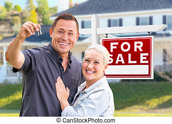Young Adult Couple With House Keys In Front of Home and For Sale Real Estate Sign