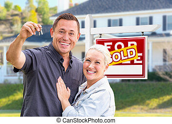 Young Adult Couple With House Keys In Front of Home and Sold For Sale Real Estate Sign