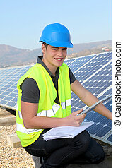 Young adult doing professional training on solar panels plant
