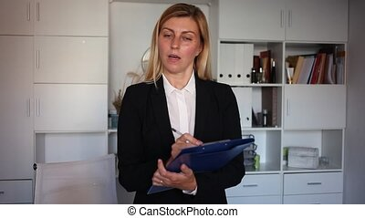 Young adult female assistant standing with clipboard and making notes in modern office. High quality FullHD footage