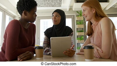 Young adult female friends hanging out in a cafe