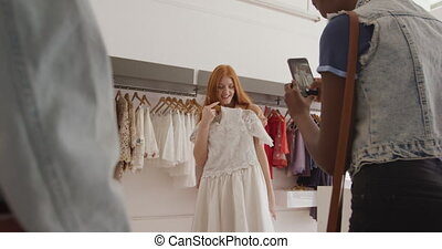 Young adult female friends in a clothes shop