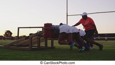 Young adult female rugby players training - Side view of a ...