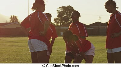 Young adult female rugby team - Side view of a team of young...