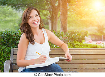 Young Adult Female Student with Pencil on Bench Outdoors