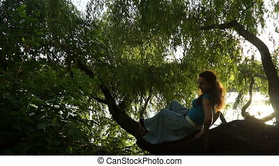 Young adult lying on a tree resting