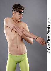 Young adult male swimmer stretching. Studio shot over gray.
