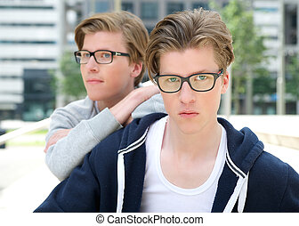Young adult male twins posing outdoors