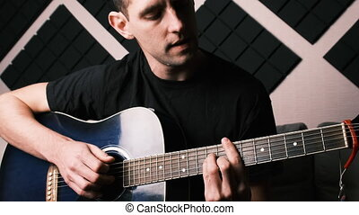 Young adult man playing acoustic guitar and sings while sitting on sofa in home recording studio. Recording an electric acoustic guitar at home. A guy in a stylish room made of acoustic foam. Blogger teaches to play