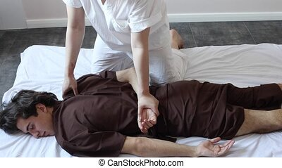 Young adult man relaxing during massage lying  in spa salon