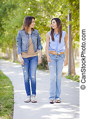 Young Adult Mixed Race Twin Sisters Walking Together