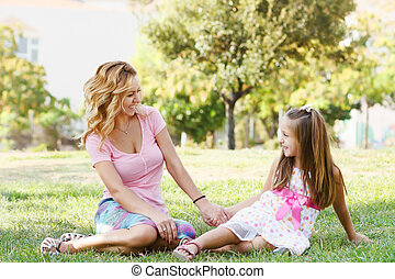 Young adult mother and little daughter smiling in park