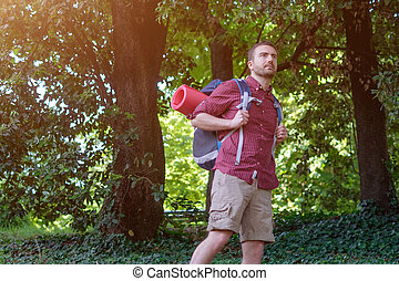 young adult traveler walking in a forest for a trip