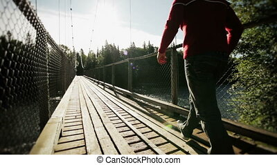 Young Adult Walking on a Hanging Bridge