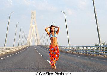 Young adult walking over  bridge