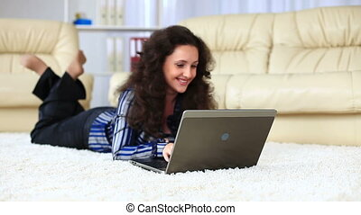 Young adult with laptop lying