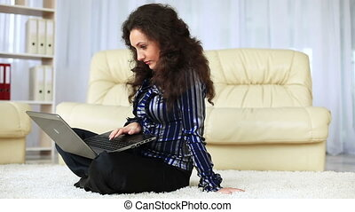 Young adult with laptop on carpet