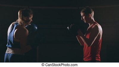 Young adult woman doing kickboxing training with her coach....