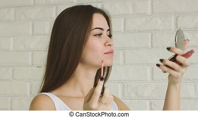 Young adult woman doing makeup by herself