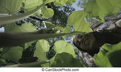 Young Adult Woman Fooling with Huge Leaves - Young adult...