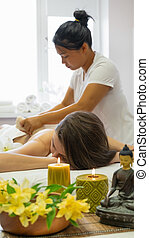 Female masseur using herbal compresses to massage the woman shoulder and back at the beauty parlor