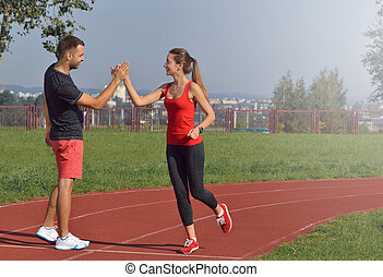 Young adult woman giving high five to partner after a run.