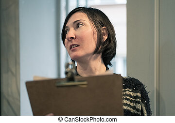 Young adult woman holding a restaurant menu wating for ...