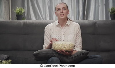 Young adult woman holding popcorn, watching tv - Young adult...