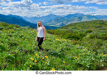 Young adult woman in alpine meadows. Happy smiling girl.