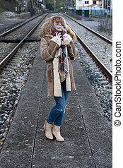 Young adult woman in casual fashion on train tracks