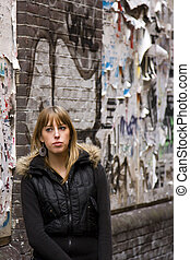 Young Adult Woman Standing Against Torn Advertisements