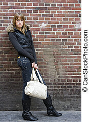 Young Adult Woman Standing with Purse in Hand