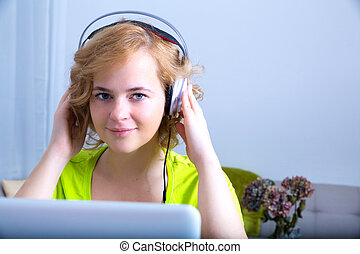 Young adult woman with headphones in front of a laptop