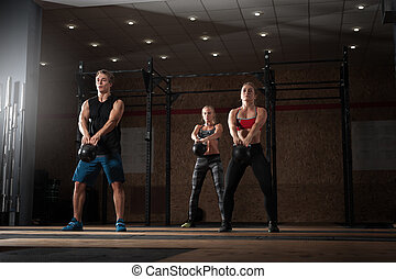 Young adults doing exercises with kettle bells