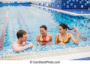 Young adults having fun talking in swimming pool indoors.