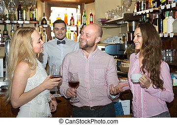 Group of cheerful smiling young adults hanging out in bar with drinks